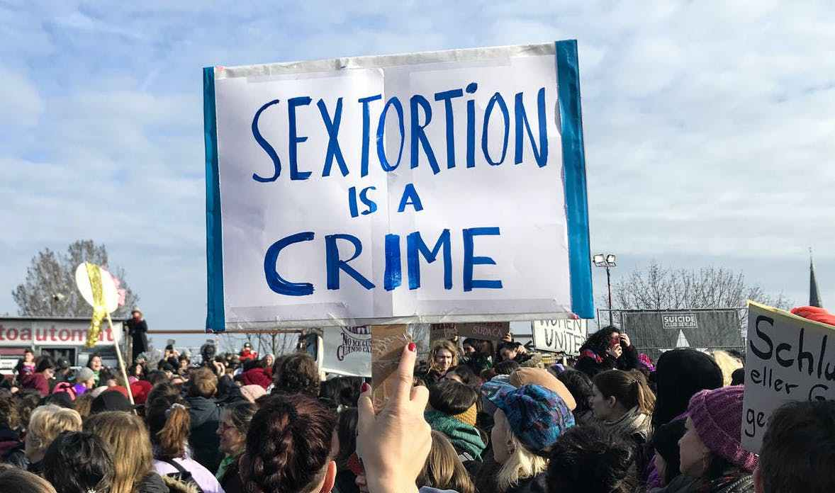 "Banner at a march saying: ""Sextortion is a crime"""